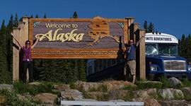 Schild mit Hinweis auf Alaska und altem Schulbus