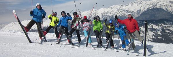 Skigruppe mit aufgestelllten Skiern vor Bergkulisse