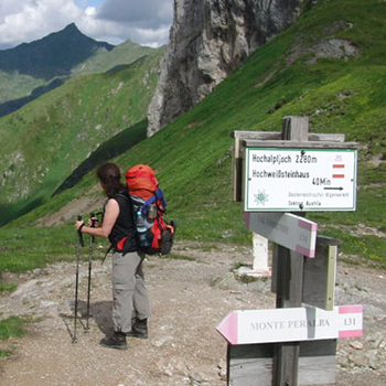 Wanderin mit Rucksack vor Bergkulisse und Hinweisschildern